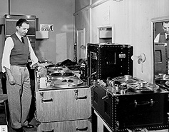 "John T.""Jack"" Mullin seen above in 1949 with the Ampex 200-A and the new Ampex 300 in portable cases• head blocks showing original tape backing facing in.  This was later changed to the backing facing out as it remained throughout the remainder of reel to reel production."