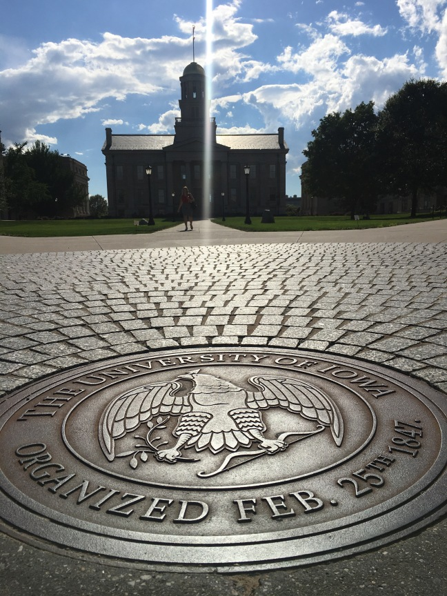 Photograph of Old Iowa State Capitol with university seal on sidewalk in foreground