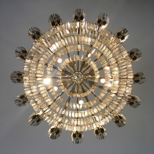 Photograph of a chandelier taken from directly below so that it appears as a sunburst